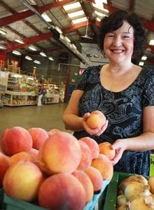 Denise at farmers market with peaches