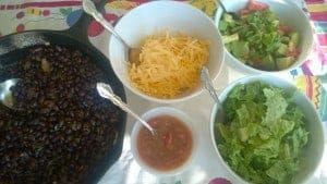 Top off a black bean taco with salsa, cheese, and guacamole.