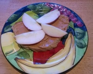 An open faced peanut butter sandwich with sliced apples