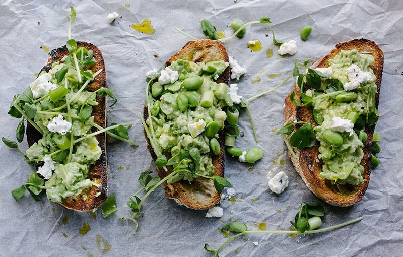 A sheet pan of avocado toast with veggie toppings